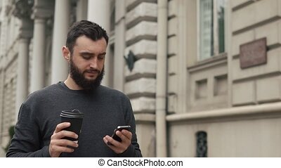 Happy beard young man texting on smartphone and drinking coffee in the street at sunset. He walks down the street, motion camera