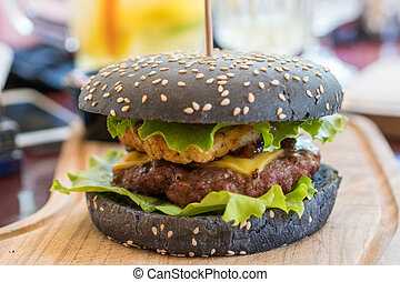 Gourmet black burger with beef, cheddar cheese, hash brown...