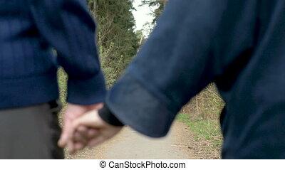 A beautiful elderly couple, walking in the park, talking...
