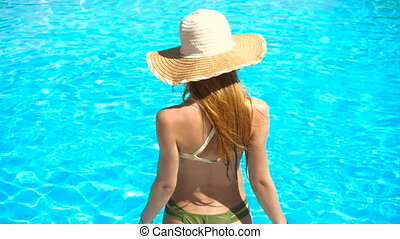 young girl in sexy bathing suit and hat walks into the water...