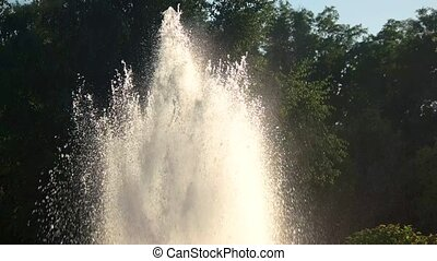 Sunshine and fountain. Splashes of water in motion.
