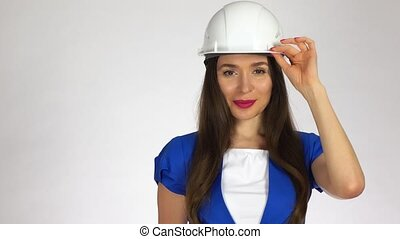 Portrait of smiling female construction engineer or architect in hard hat against white background. 4K shot