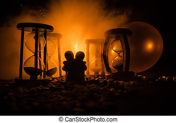 Time and love concept. Silhouettes of toy ceramic figures hugging between hourglasses in dark lighted background with fog