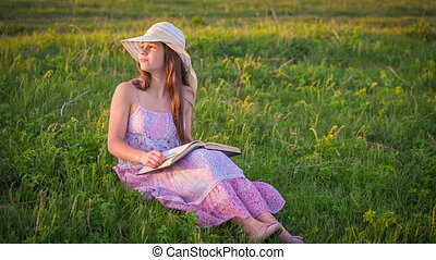 Romantic girl reading the book on green meadow on sunset