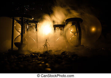 Time concept. Silhouette of a man standing between hourglasses with smoke and lights on a dark background.