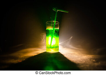 Glass of green cocktail with straw on dark background with...