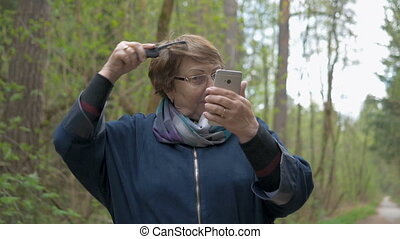 An elderly beautiful woman looks into a smartphone and...