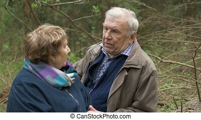 An elderly, beautiful couple sitting in a wood, on a sawn...