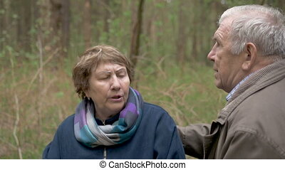 An elderly, beautiful couple sitting in a wood, on a sawn wood. They tenderly talk, hug, in love look at each other. Slow motion