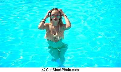 beautiful girl in a bathing suit stands in the pool and...