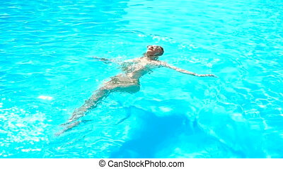 beautiful young girl in glasses floats on her back in a pool...