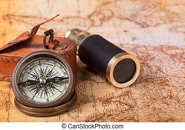 Brass Compass on a Map - Brass compass and telescope on a...