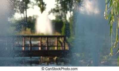 Blurred fountains and bridge. Blurry summer backdrop.