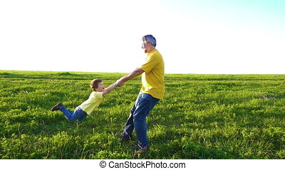 Father rotating his son holding his hands on green meadow,...
