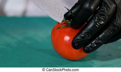 Red ripe tomato cut in half by the chef's culinary knife