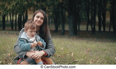 young beautiful mother playing with her cute little son, who is sitting on her lap in the autumn park 4k