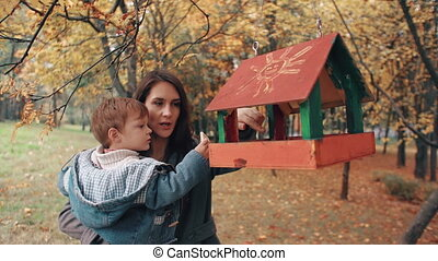young mother holding his cute little son, the boy puts food in the bird feeder in an amazing autumn park 4k