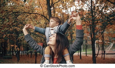 beautiful young mother holds on the shoulders a cute little...