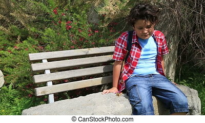 Child sitting on a park bench - Portrait of young happy teen...