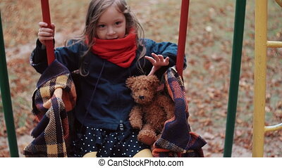 cute little girl on a old swing with her teddy bear in...