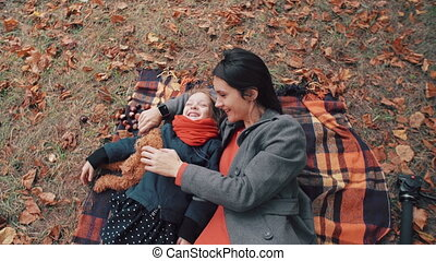 beautiful mother with her cute little daughter lying on the plaid have fun in autumn park 4k