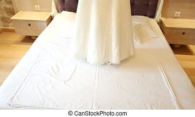 The wedding dress of the bride hangs over the bed....