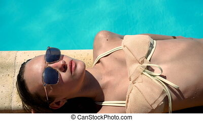 sexy woman in sunglasses and swimsuit lying and sunbathing -...