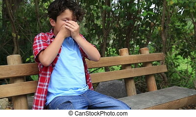 Child sneezing - Boy with allergic rhinitis sitting on a...