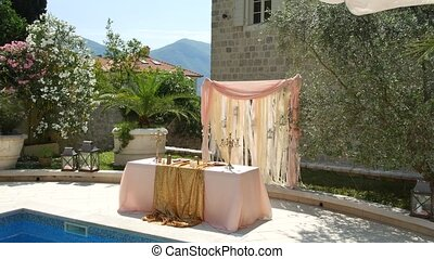 A table at the wedding banquet near the pool. Wedding decoration