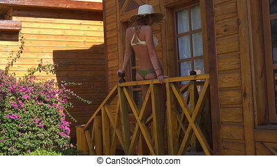 young woman in straw hat and sexy bikini sits on the porch -...