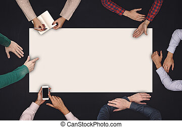 Teamwork and cooperation concept - top view of six people drawing or writing on a large white blank sheet of paper on blackboard.