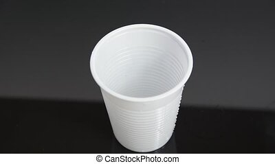 Water pouring down into plastic cup - Water pouring down...