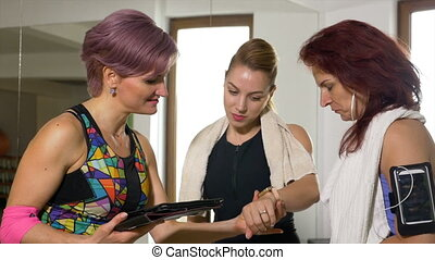 Fitness personal trainer checking woman smartwatch before explaining plan of exercises on the tablet pc