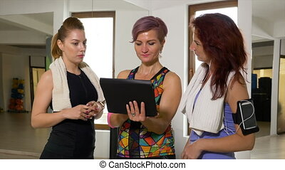 Coach doing wellness training to women using smart devices...