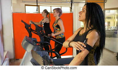 Fitness instructor training on the treadmill setting up smartphone tracking app