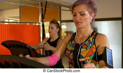 Adult woman with fitness tracker wearable technology doing cardio exercise at gym club
