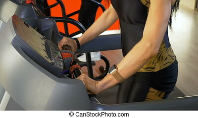 Woman checking heart rate on smartwatch during fitness exercise on treadmill