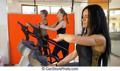 Woman trainer in gym checking pulse on smartwatch and...
