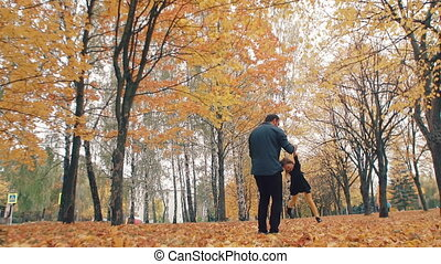 young handsome father turns his cute little daughter around holding her hand in autumn park slow mo
