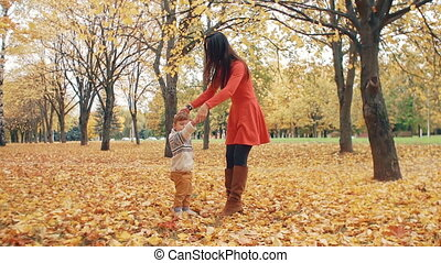 young beautiful mother turns her cute little son around...