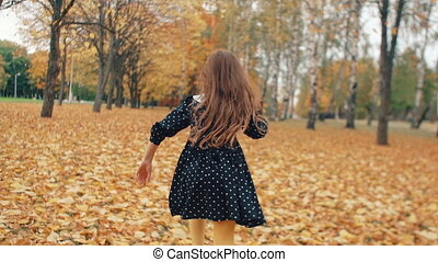 happy cute little girl with curly hair, in dress with polka...