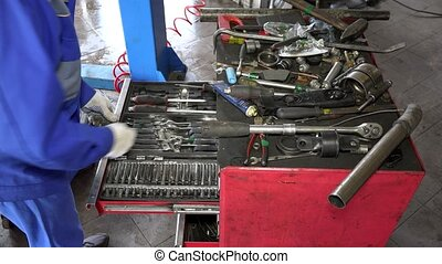 professional mechanic looking for tools in drawer box at car...