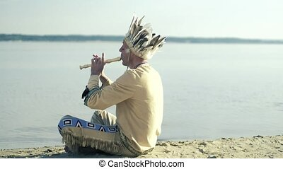 An Indian in a national costume plays a flute on the river...