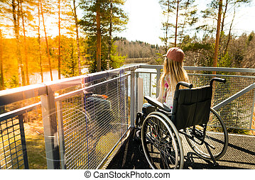 Young girl in a wheelchair on a balcony looking at the...