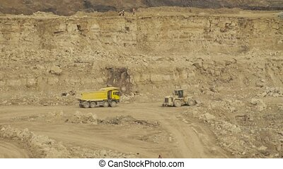 Truck driving in quarry. Small figures of people at the top...