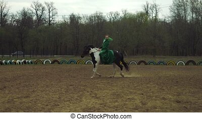 A woman in a green suit is riding a horse