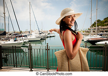 wman walks a city on the beach on hot summer day un beautiful red dress with hat.