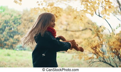close-up funny cheerful cute little girl spinning with her toy, teddy bear yellow in the amazing autumn park slow motion