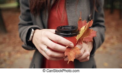 Autumn. hands of young stylish woman holding a paper cup of...