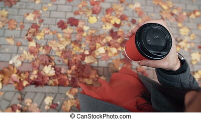 Autumn. Top view of young stylish woman holding a paper cup...